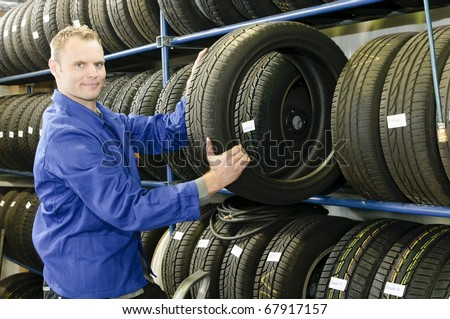 Car mechanic in blue overalls pulls a tire from the tire store in the garage - stock photo