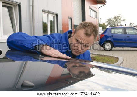 Car mechanic in blue overalls sweeps his hand across the hood of a car and check the painting in the sunlight. - stock photo