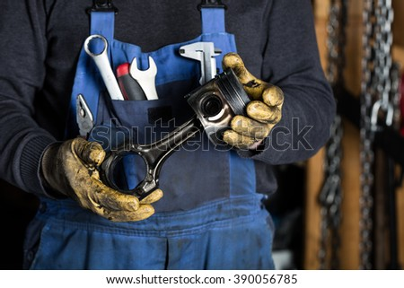 Car mechanic in garage with old car engine piston. Concept - stock photo