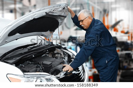 Car mechanic in uniform. Auto repair service. - stock photo