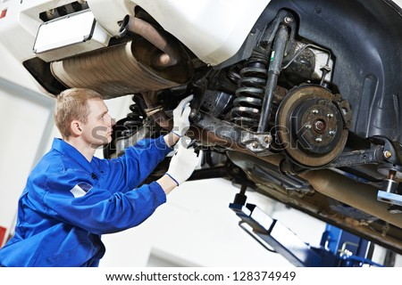 car mechanic inspecting car wheel and suspension detail of lifted automobile at repair service station - stock photo