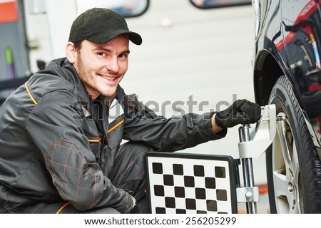 car mechanic installing sensor during suspension adjustment and automobile wheel alignment work at repair service station - stock photo