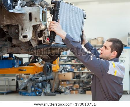 Car mechanic is Changing radiator - stock photo