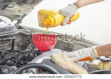 Car mechanic pouring new oil to engine. - stock photo