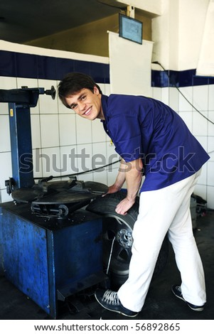 car mechanic repairing tire at the car repair shop