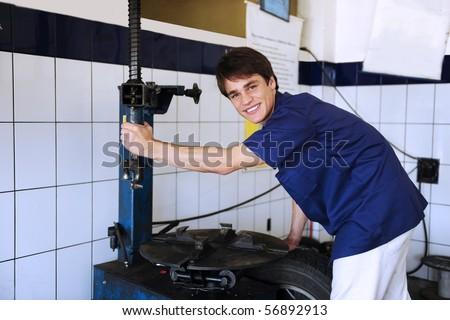 car mechanic repairing tire at the car repair shop - stock photo