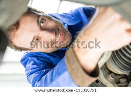Car mechanic repairs the brakes of an automobile on a hydraulic lift