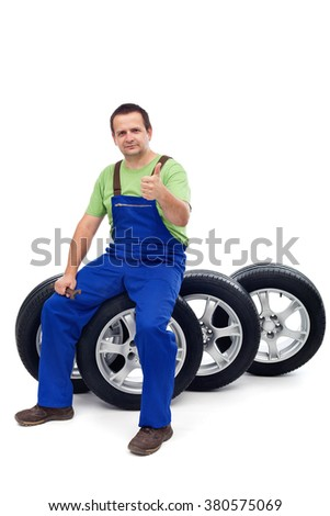 Car mechanic with a set of new tires giving thumbs-up sign - isolated on white
