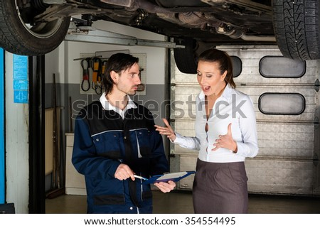 Car mechanic with attractive but angry female customer going through maintenance checklist in garage - apparently the efforts are overpriced since the woman is screaming at the mechanic. - stock photo