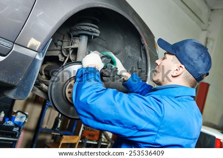 car mechanic worker repairing brakes of lifted automobile at auto repair garage shop station - stock photo