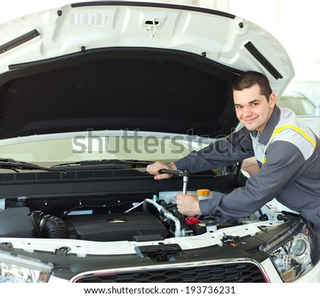Car mechanic working in auto repair service with engine. - stock photo