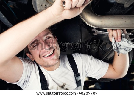 Car mechanic working under the car smiling Car service - stock photo