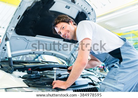 car mechanic working with tool in service workshop - stock photo