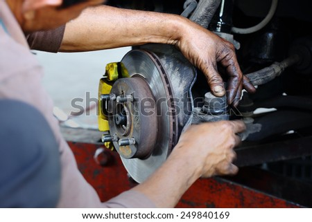 Car mechanician working on automobile disc brake system repair - stock photo