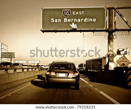 Car merging onto packed highway in Los Angeles during rush hour on a hot day. - stock photo