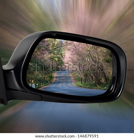 Car Mirror on The Road with Concept of Speed - stock photo