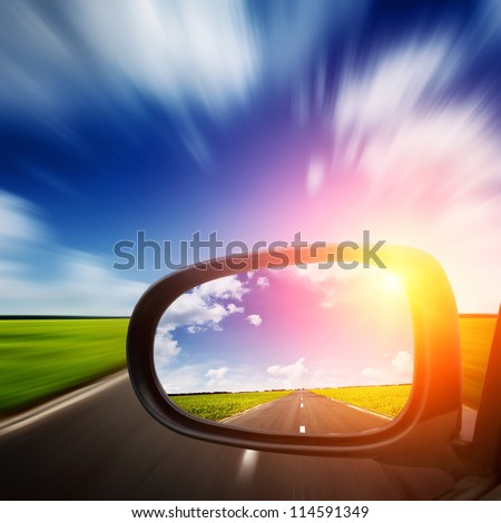 car mirror with blue sky above road - stock photo