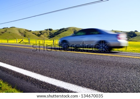 car moving quickly along a road from a low point of view - stock photo