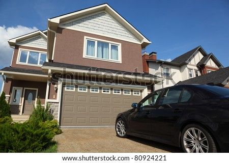 Car near the garage of new two-storied brown cottage with white roof - stock photo