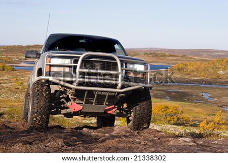 car off-road stands near the lake on earth - stock photo