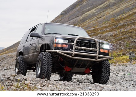 car off-road with switched on headlights on mountain background - stock photo
