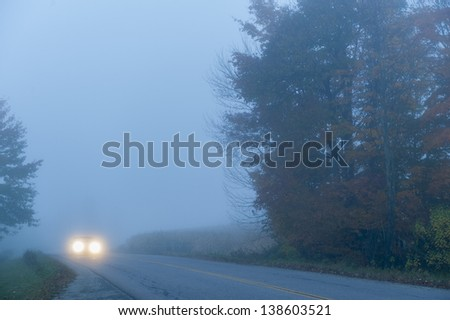 Car on a lonely foggy road in the early morning, Stowe, Vermont, USA - stock photo