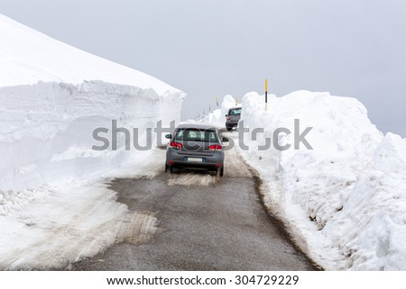 Car on a snowy street souranded by two walls of snow. - stock photo