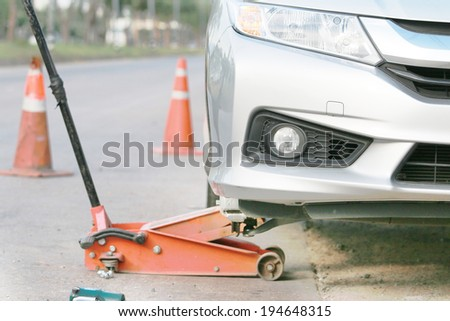 car on jack for changing wheel tire. - stock photo