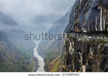 Car on road in Himalayas mountains above precipice