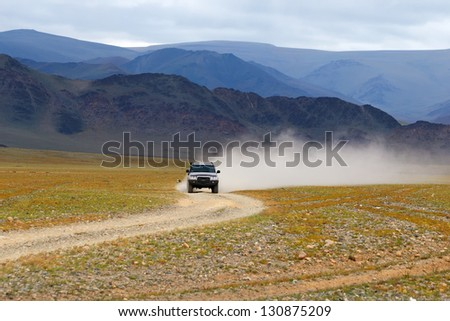 Car on road in the desert mountain of the Mongolia - stock photo