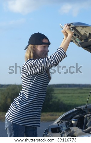 Car on roadside and young woman attempting to repair it - stock photo