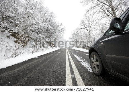 Car on snowy winter road. - stock photo