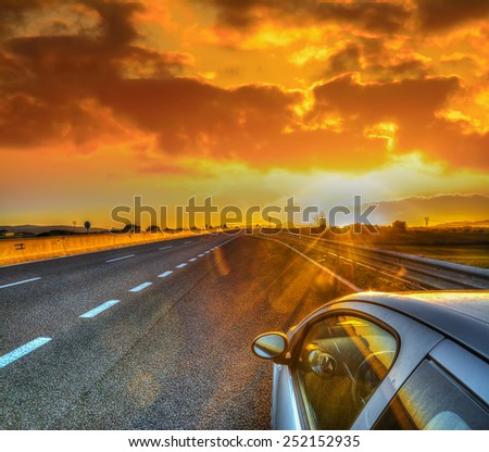 car on the edge of the road under a scenic sky at sunset. Processed for hdr tone mapping effect. - stock photo