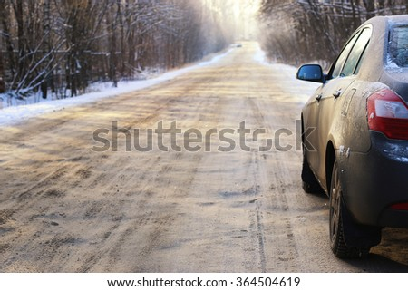 car on the road in winter - stock photo