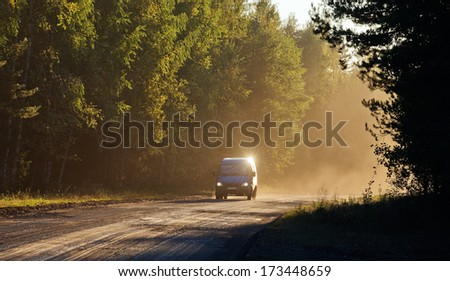 Car on the Road through forest in sunset fog.  - stock photo