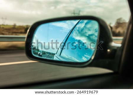 car on the road with motion blur background and rear view mirror - stock photo