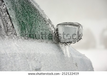 Car on the street covered by icy rain. - stock photo