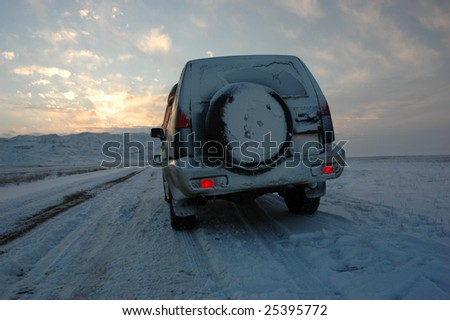 car on winter road - stock photo