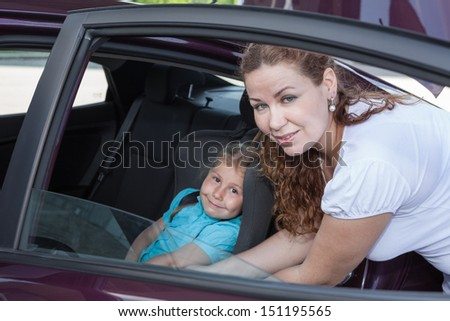 Car opened door with helping mother to fast small child for journey - stock photo