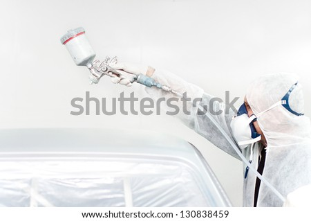 car painter working on a car in a special booth - stock photo