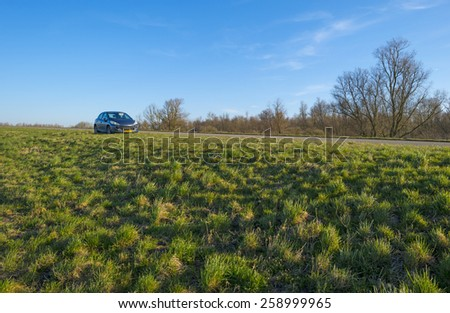 Car parked along a dike in winter - stock photo
