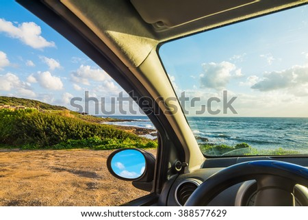 Car parked by the sea on a cloudy day - stock photo