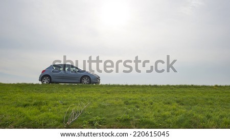 Car parked on a road along a dike - stock photo