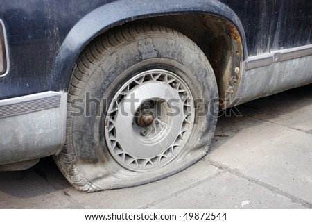 Car parked on a roadway with a flat tire - stock photo