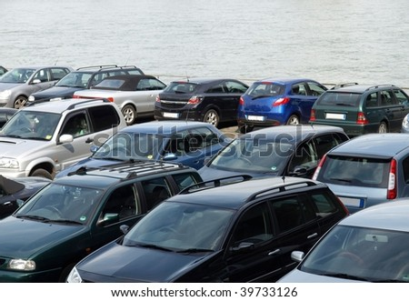 Car parking with cars parked on the riverside - stock photo
