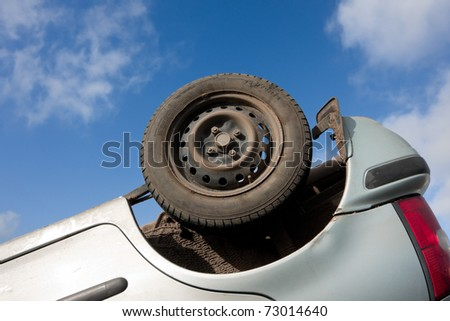 car part, turned upside-down after road collision - stock photo