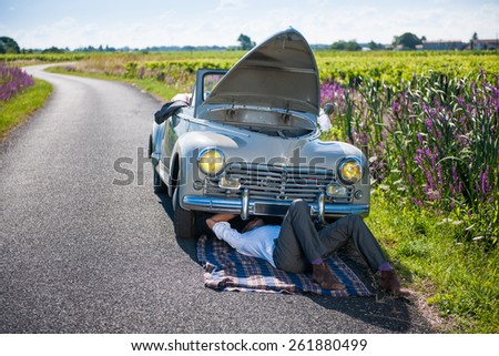 Car problems on a country road. A man in a suit is trying to fix his retro car - stock photo