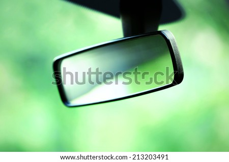 Car rear view mirror on green background - stock photo