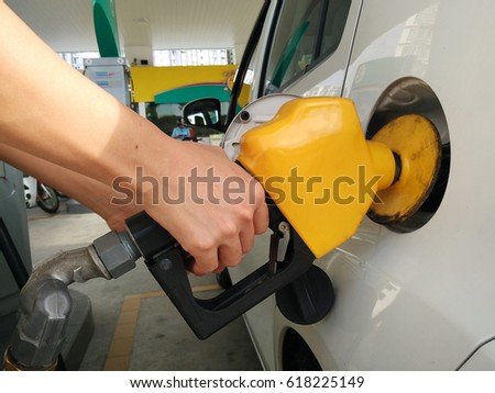 Car refilling fuel in petrol station with yellow color dispenser