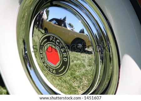 Car Reflected in Chrome Hubcap with White Wall Tires - stock photo